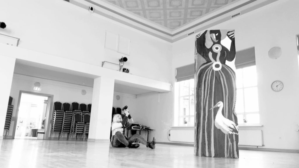 Black and white Image of Ieva Caruka and her artwork in Marupe Culture House.